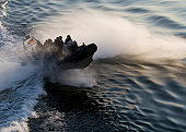 A (German GSG 9) special forces police inflatable rigid hull boat hitting the wake of a ship and creating a lot of spray.