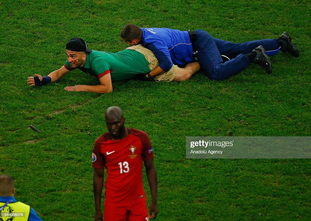 A police tries to catch a pitch invader during the Euro 2016 quarter-final football match between Poland and Portugal at the Stade Velodrome in Marseille, France on June 30, 2016.