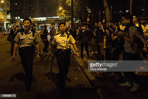 Police try to chase down prodemocracy activists who were trying to block a main road in Mong Kok on November 29 2014 in Hong Kong Clashes between...