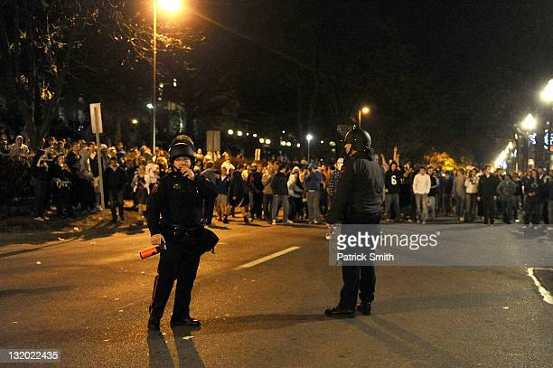 Police try to control students and those in the community as they fill the streets and react after football head coach Joe Paterno was fired during...