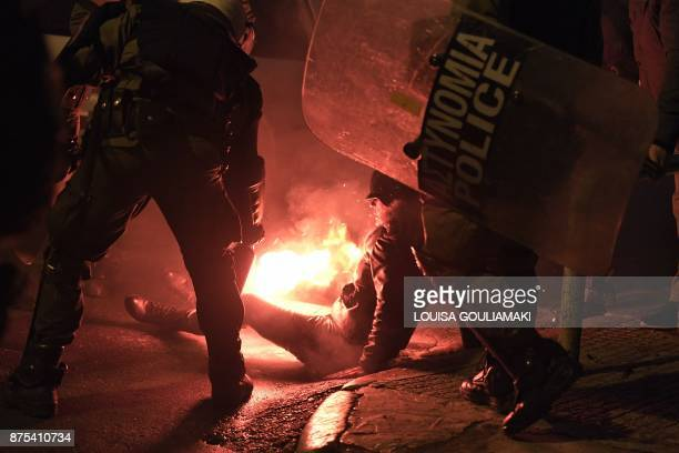 TOPSHOT Police try to extinguish a woman's clothing ignited by a flare rocket on November 17 2017 in Athens during clashes following a rally...