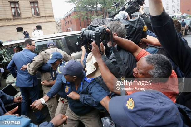 Police try to hold back the media as Carl Pistorius the brother of Oscar Pistorius arrives at North Gauteng High Court on March 3 2014 in Pretoria...