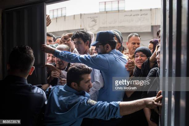Police try to keep people from forcing their way into a voting station on September 25 2017 in Erbil Iraq Despite strong objection from neighboring...