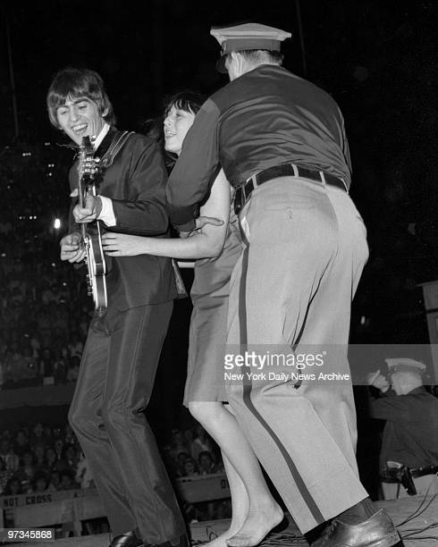 Police try to restrain Mary Smith a 17yearold fan from Connecticut as she holds on to Beatle George Harrison during Forest Hills Stadium Concert
