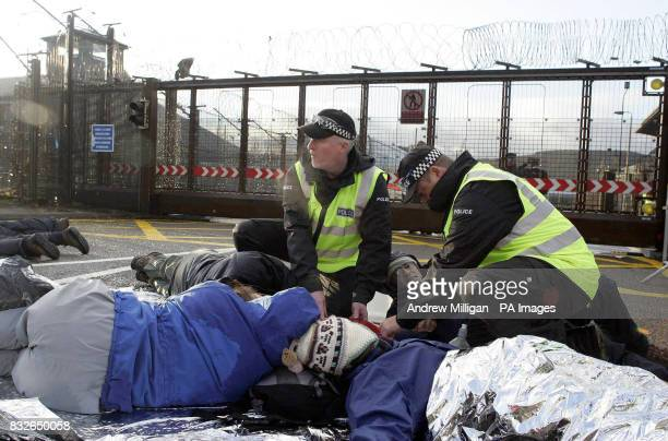 Police try to separate protestors as they block the entrance to Faslane on the River Clyde Scotland the Trident nuclear submarine base