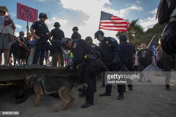 Police use a bombsniffing dog to check on packs owned by demonstrators at an 'America First' demonstration on August 20 2017 in Laguna Beach...