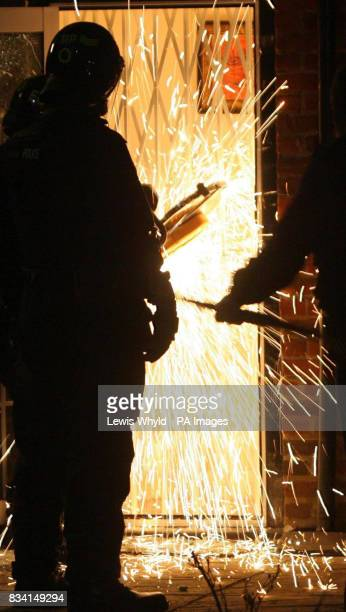 Police use an angle grinder to break through a fortified door and gain access to the luxury home of one of the suspected kingpins of a 100 million...