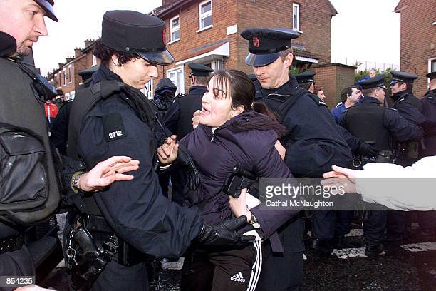 Police use force to detain a woman during a security operation near Holy Cross primary school November 12 2001 in the Ardoyne area of north Belfast...