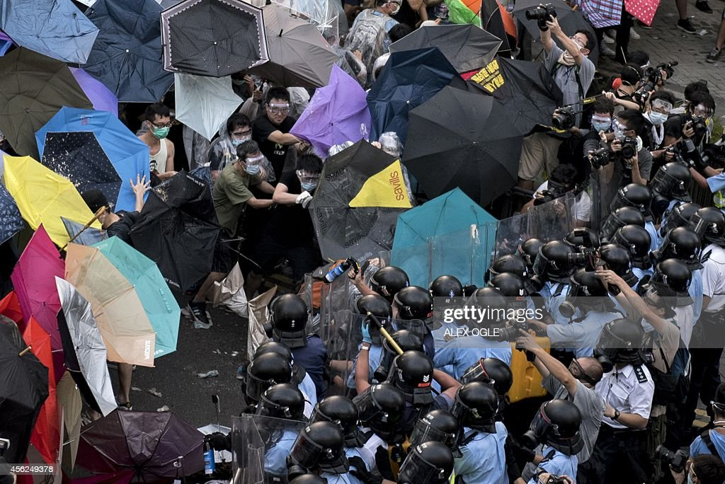 Police use pepper spray in an attempt to disperse prodemocracy protesters near the government headquarters in Hong Kong on September 28 2014 Police...