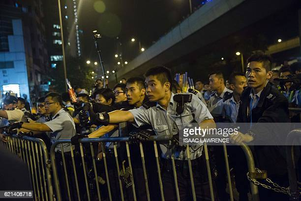Police use pepper spray to stop protesters charging outside the Chinese Liason Office in Hong Kong on November 6 during a protest against an expected...