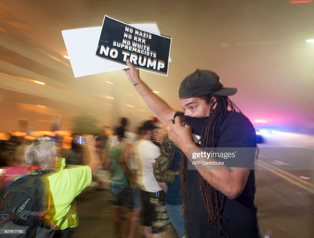 Police use tear gas to break up protesters gathered outside of the Phoenix, Arizona, Convention Center where US President Donald Trump spoke at a 'Make America Great Again' rally on August 22, 2017. / AFP PHOTO / Laura Segall