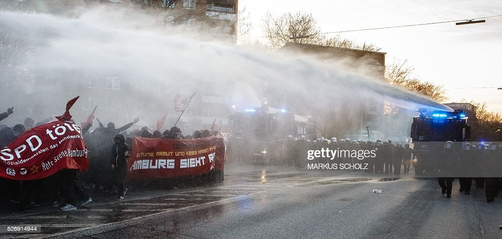Police use water cannon against people taking part in the traditional 'Revolutionary' May Day demonstration in Hamburg, northern Germany, on May 1, 2016. Thousands of leftists, trade unionists and workers took to the streets through out the country on the occasion of International labour day. / AFP / dpa / Markus Scholz / Germany OUT