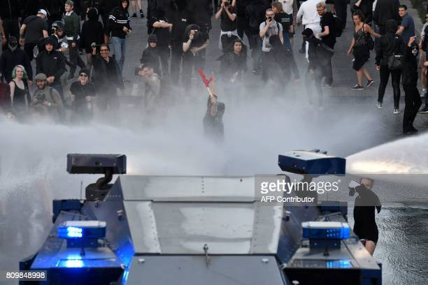 Police use water cannon torwards a protester with a red flag during the 'Welcome to Hell' rally against the G20 summit in Hamburg northern Germany on...