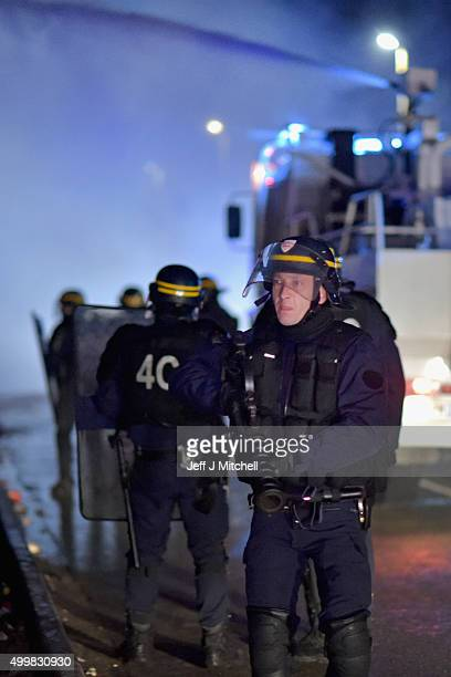 Police use water canon and tear gas on migrants at the entrance to camp known as the 'New Jungle' on December 4 2015 in Calais France Thousands of...