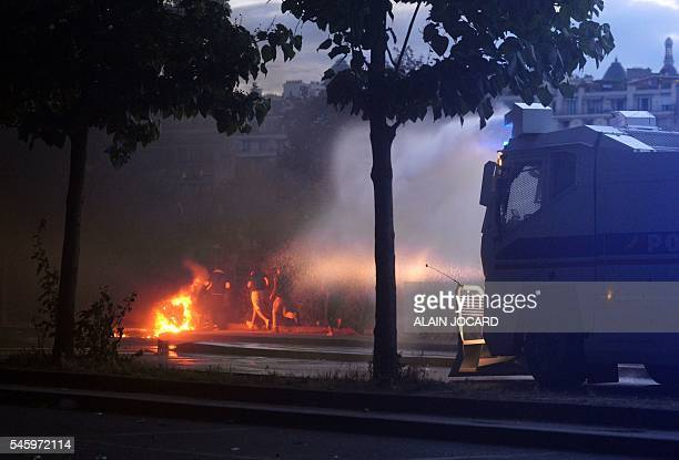 Police uses water cannon to extinguish fire during clashes prior to the Euro 2016 final football match between Portugal and France near the...