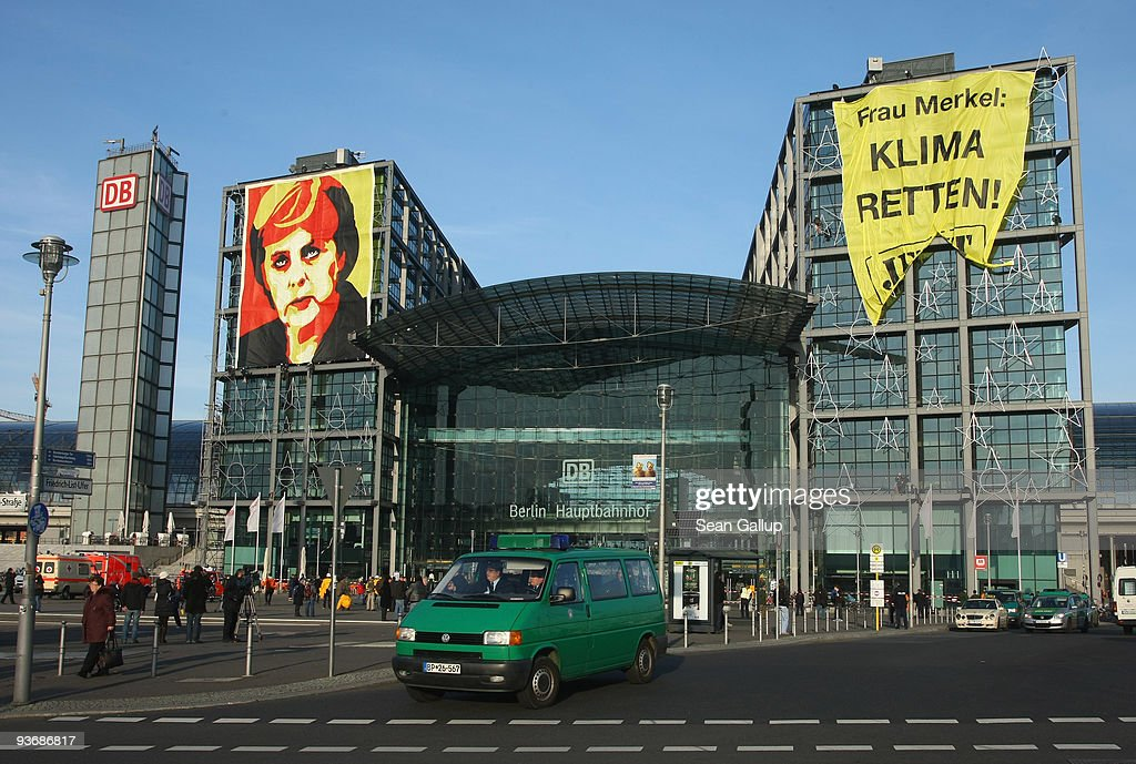 A police van drives past giant banners showing German Chancellor <a gi-track='captionPersonalityLinkClicked' href=/galleries/search?phrase=Angela+Merkel&family=editorial&specificpeople=202161 ng-click='$event.stopPropagation()'>Angela Merkel</a> that read: 'Climate Protection Now! Copenhagen 2009' (L) and 'Mrs. Merkel: Save the Climate! Now!' hanging from Hauptbahnhof train station on December 3, 2009 in Berlin, Germany. The banners, hung by Greenpeace activists, refers to the upcoming summit on climate change in Copenhagen, where Chancellor Merkel will lead the delegation representing Germany.