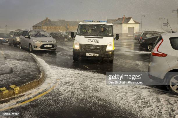 A police van makes its way through the sea spray and foam on the Esplanade Porthcawl south Wales as the region continues to be battered high winds...