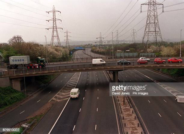A police van speeds along a deserted motorway as diverted traffic queues on a flyover above the M6 motorway at Junction 7 north of Birmingham Three...