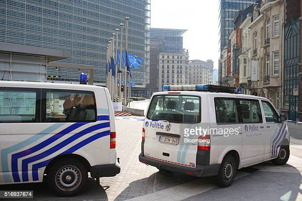 Police vans sit parked as flags of the European Union fly at halfmast outside the European Council building in Brussels Belgium on Tuesday March 22...