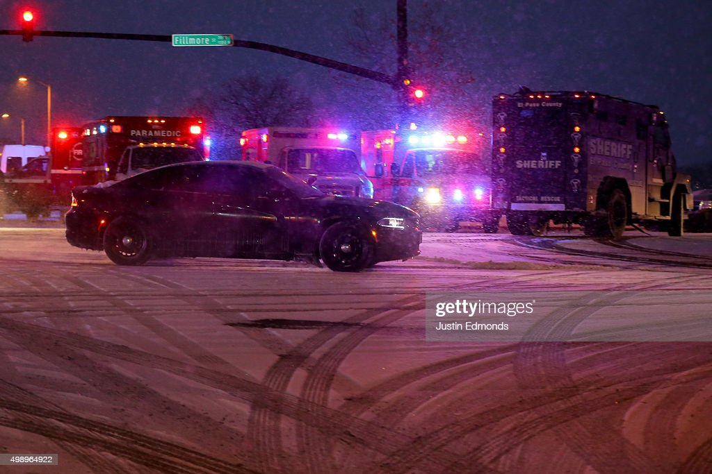 A police vehicle carrying a suspect drives away from the scene during an active shooter situation outside a Planned Parenthood facility where an...