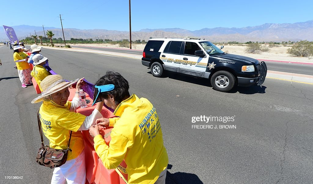 A police vehicle drives by on security patrol as Falungong practioners place banners on a barricade to face vehicular traffic from a cordoned off protest zone across from where President Barack Obama is due to meet his Chinese counterpart Xi Jinping in the California desert community of Rancho Mirage, a little over 100 hundred miles east of Los Angeles, on June 7, 2013, where they were joined by Falun Gong practioners in protesting the brutal repression of China's ruling Communist Party. Xi, the Chinese leader arrived in southern California the previous evening and stayed in a nearby hotel, according to the local Desert Sun newspaper, ahead of what was planned as an unusually relaxed US-China summit. AFP PHOTO/Federic J. BROWN