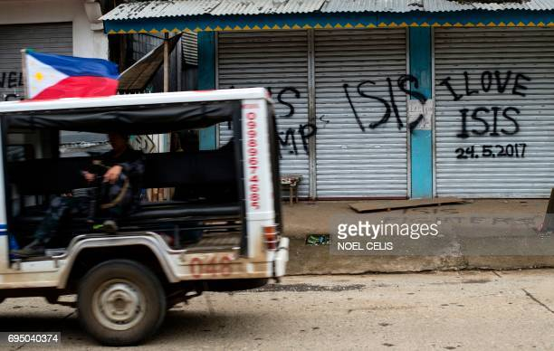 A police vehicle drives past shuttered shopfronts sprayed with proIslamic State group grafitti in Marawi on the southern island of Mindanao on June...