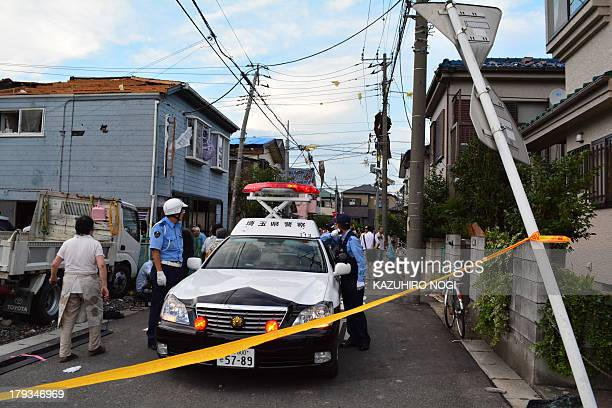A police vehicle is parked in the middle the street next to damaged houses after a tornado tore through parts of the city of Koshigaya Saitama...