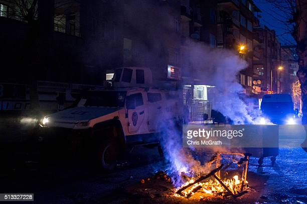 A police vehicle passes fires lit by protesters on March 2 2016 in Diyarbakir Turkey Thousands of people protested against governmentimposed curfews...