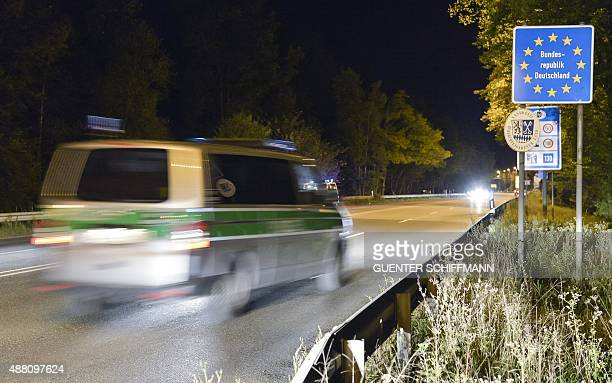 A police vehicle passes the German border sign at the border between Germany and Austria in the southern German city of Freilassing on September 13...