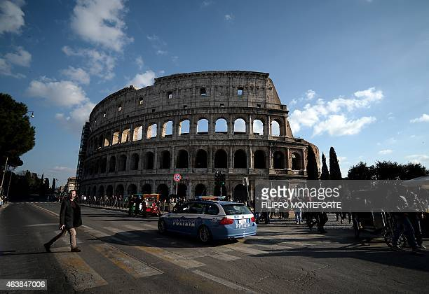 A police vehicle patrols near the Colosseum on February 19 2015 in Rome Security at the Vatican and across Italy has been stepped up because of a...