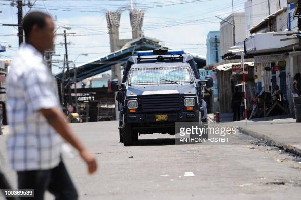 A police vehicle patrols the street on May 24 2010 in Kingston Jamaica after two police officers were killed after coming under attack amid spreading...