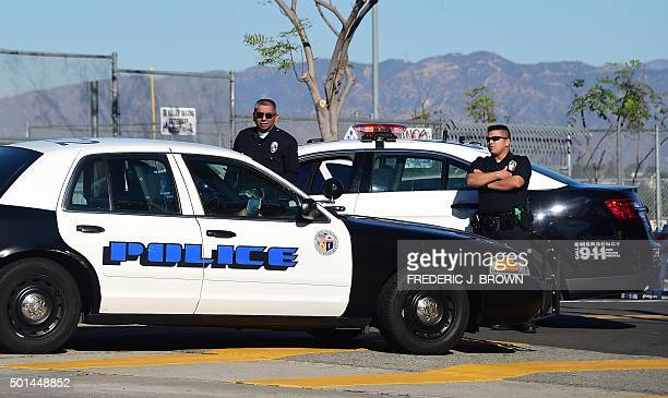 A police vehicle pulls up next to two officers standing at their vehicle outside a closed school near downtown Los Angeles on December 15 2015 Los...