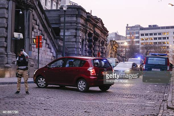 Police vehicles are parked near the Palace of Justice in Brussels on January 21 2015 as heavy security measures were deployed all around the court...