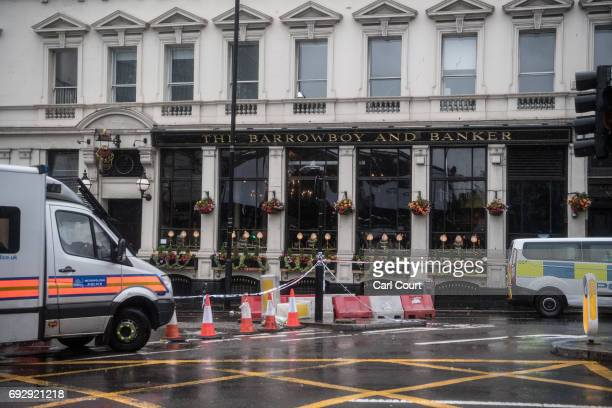Police vehicles are parked outside the Barrowboy and Banker pub near the scene where a van was driven into a wall during Saturday's terrorist attack...
