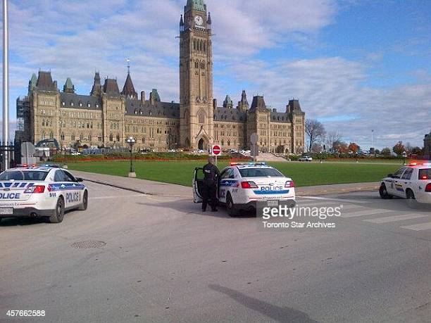 Police vehicles are pictured in front of Parliament Hill in Ottawa on Wednesday Oct22 2014 A Canadian soldier standing guard at the National War...