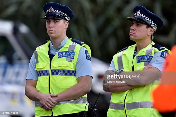 Police wait for Greenpeace activists to absail back down from the roof at Parliament House on June 25 2015 in Wellington New Zealand Four Greenpeace...