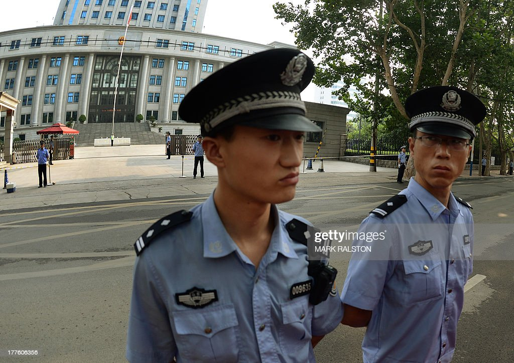 Police wait for the convoy carrying disgraced politician Bo Xilai and Wang Lijun arrives for the fourth day of Bo's trial at the Intermediate People's Court in Jinan, Shandong Province on August 25, 2013. Once one of China's highest-flying politicians, Bo Xilai found himself in the criminal dock on trial for bribery and abuse of power in the country's highest-profile prosecution in decades. His downfall began when a British businessman was found dead in a hilltop hotel room. As the drama finally nears its conclusion, the Communist Party is touting it as proof of its intent to crack down on corruption. AFP PHOTO/Mark RALSTON