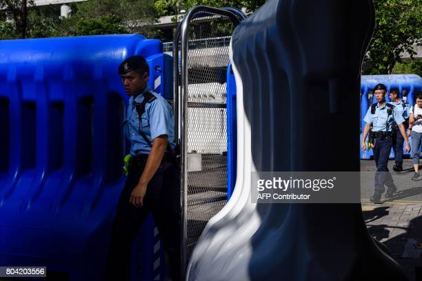 Police walk between water horse barriers set up along a road as part of security precautions for Chinese President Xi Jinping's visit to Hong Kong on...