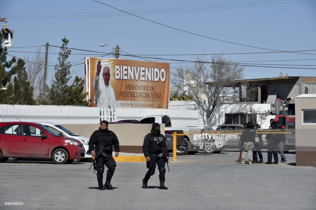 Police walk in front of a banner welcoming Pope Francis at the main entrance of the city prison in Ciudad Juarez Mexico on February 3 2016 Pope...