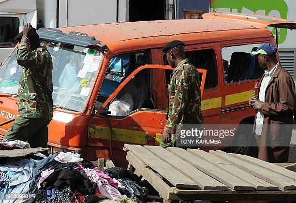 Police walk past a damaged public transport vehicle at the scene of an explosion on May 16 2014 on the outskirts of Nairobi's business district where...