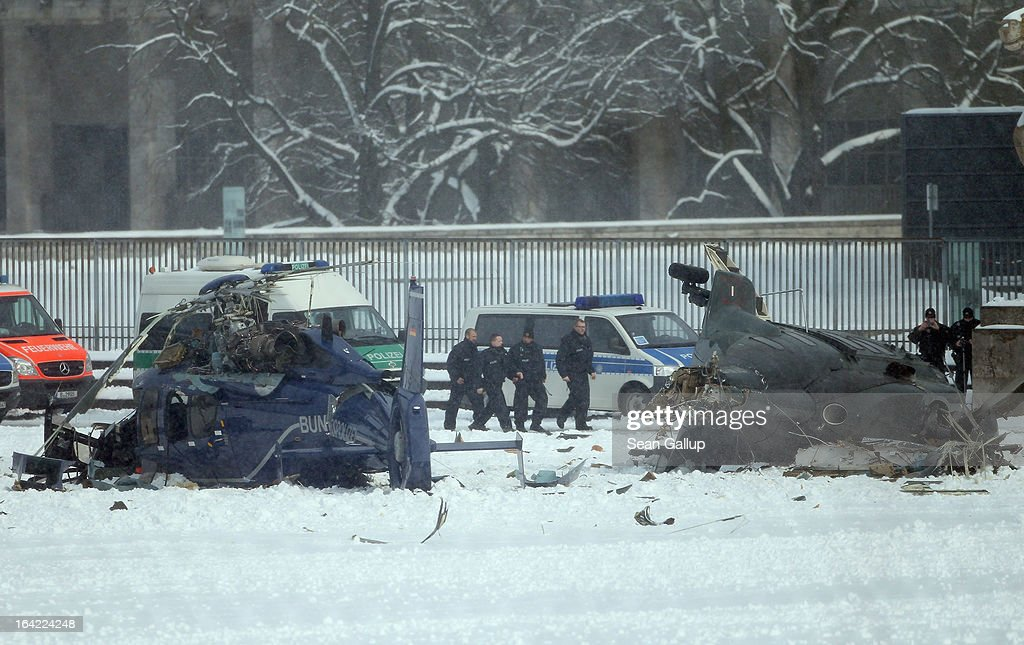 Police walk past the wreckage of two police helicopters that collided near the Olympiastadion stadium, killing one pilot and leaving several injured, on March 21, 2013 in Berlin, Germany. The helicopters were partcipating in a police exercise meant to simulate football hooligan clashes with police when the accident occured.