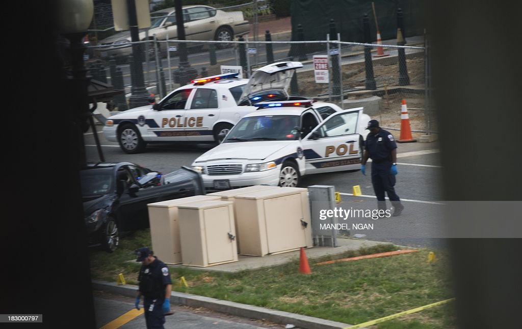 Police walk the on Constitution Ave next to a car on the median in front of the Hart Senate Office Building on October 3, 2013 in Washington, DC following reports of a shooting. AFP PHOTO/Mandel NGAN