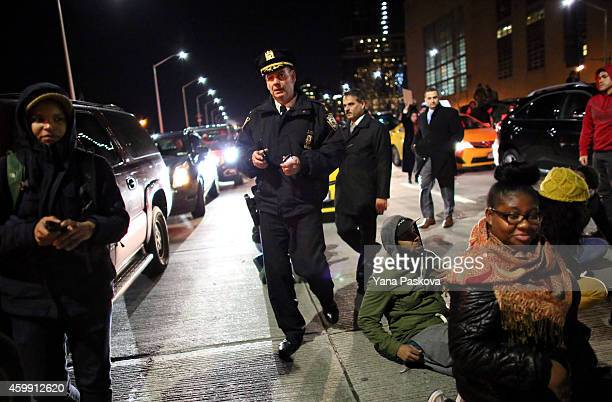 Police walk through protesters clash on the West Side Highway December 3 2014 in New York Protests began after a Grand Jury decided to not indict...