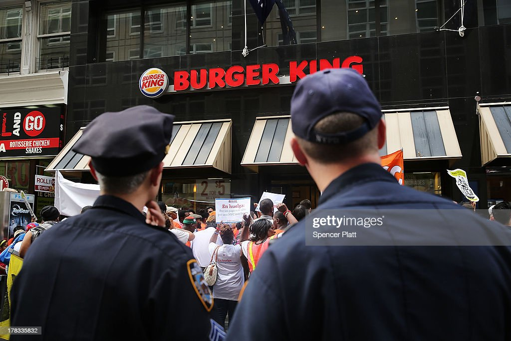 Police watch as employees and supporters demonstrate outside of a Burger King fast-food restaurant to demand higher pay and the right to form a union on August 29, 2013 in New York City. Across the country thousands of low-wage workers are expected to walk off their jobs Thursday at fast food establishments in several U.S. cities. Workers at KFC, Wendy's, Burger King, McDonald's and other restaurants are calling for a living wage of $15 an hour and the right to form a union without retaliation.