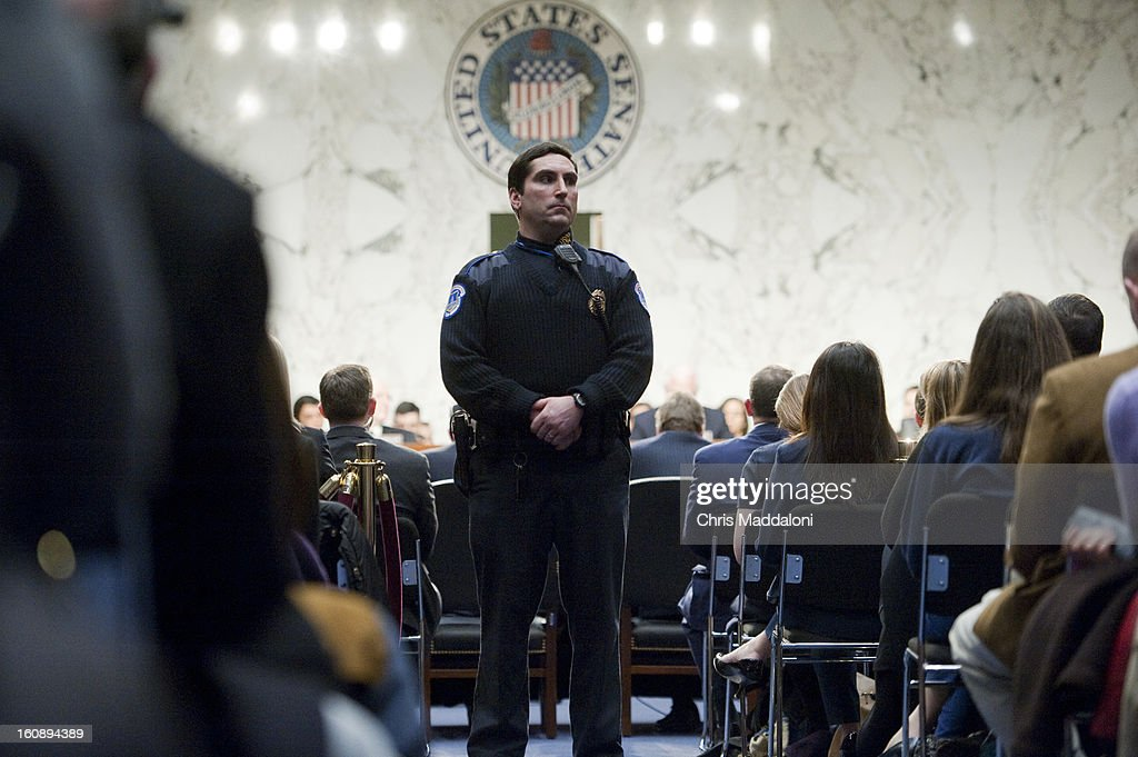 Police watch as protesters interrupt the start of a nomination hearing for U.S. Assistant to the President for Homeland Security and Counterterrorism John Brennan before the Senate Intelligence Committee. Brennan is the nominee to be the next Director of the Central Intelligence Agency, and is expected to face harsh questioning the drone targeted killing program.
