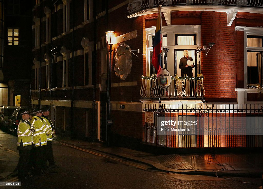 Police watch as Wikileaks founder Julian Assange speaks from the Ecuadorian Embassy on December 20, 2012 in London, England. Mr Assange has been living in the embassy since June 2012 in an attempt to avoid extradition to Sweden where he faces allegations of sexual assault.