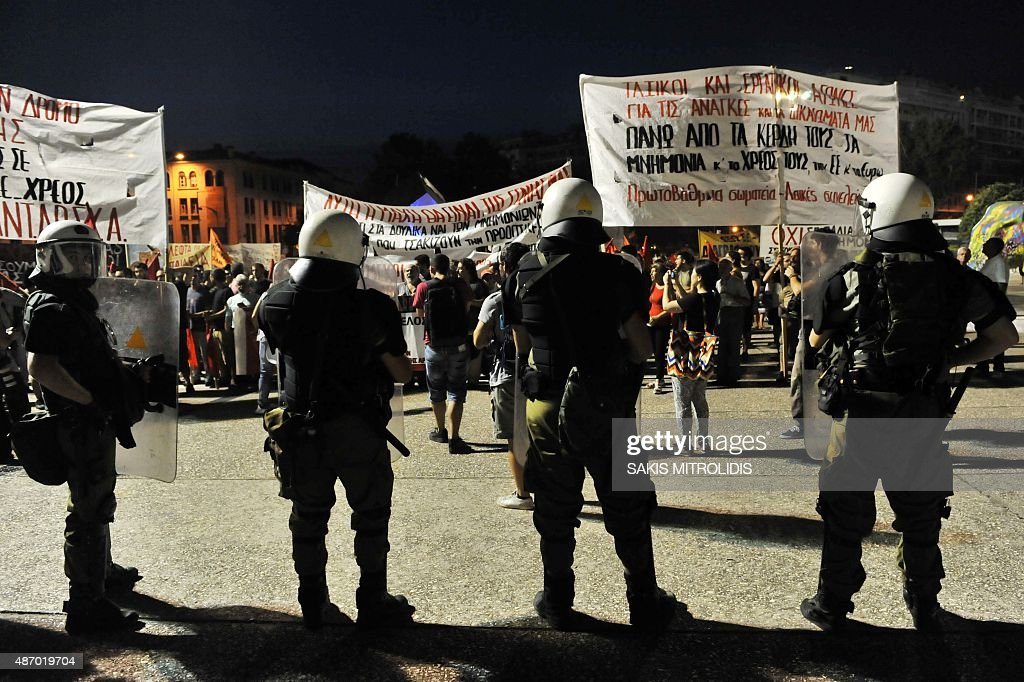 Police watch demonstrators taking part in a protest against government austerity measures and reforms of the third Greek bailout at the annual...