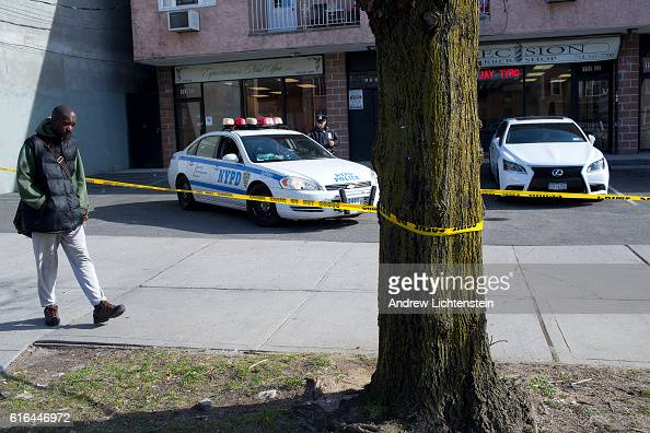 Police watch over a crime scene where Joneil Major was shot to death on the very edge of eastern New York City at Linden Boulevard and 193rd Street...
