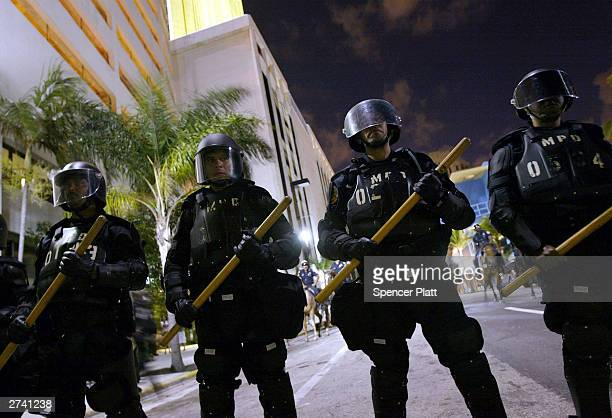 Police watch over antiglobalization protesters as they demonstrate on the second day of the summit to create a Free Trade Area of the Americas...