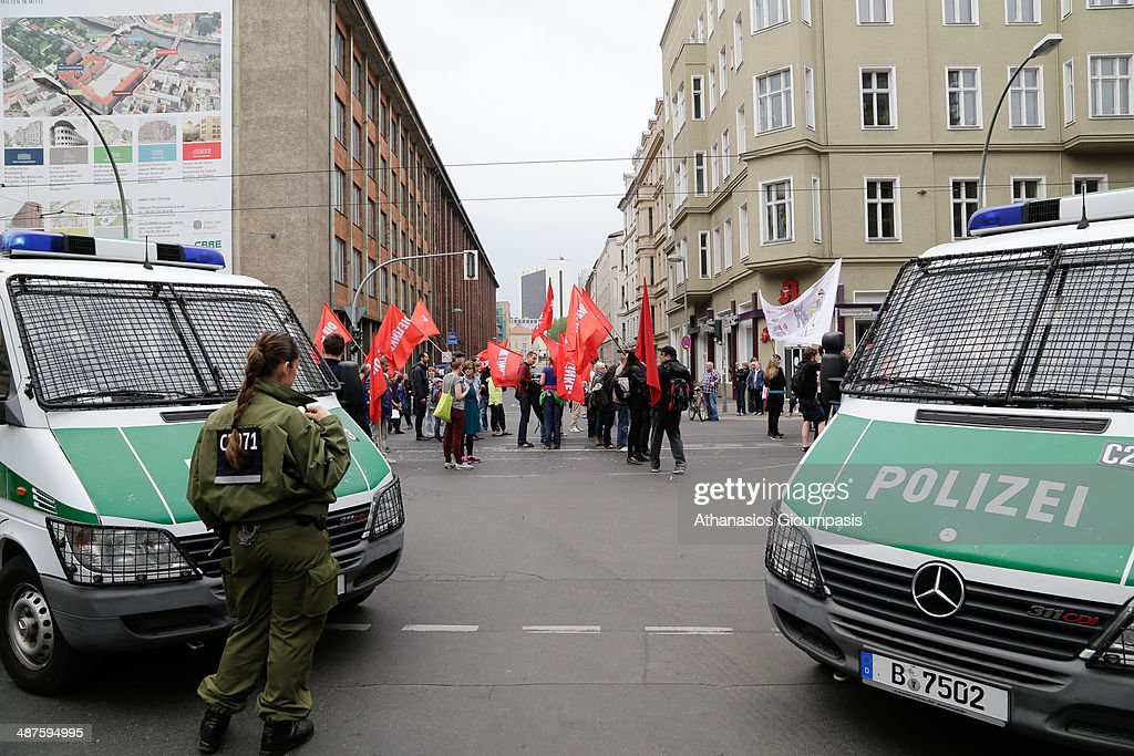 Police watch protesters arrive on May Day on May 1, 2014 in Berlin, Germany. May Day or International Workers Day was established as a public holiday after 1933 .